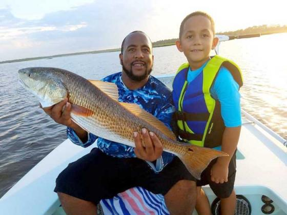 Eli Walfall and his dad, David, with a great redfish from the creeks. (photo submitted)
