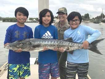 Alton and Jayden Azcona, along with Aiden Paul Florin, were so excited about their barracuda catch, they just had to show it to FWC Officer Miano at the dock. (photo courtesy of FWC)